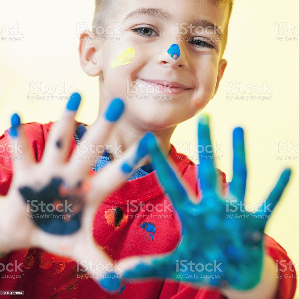 Cute little boy with dirty hands from paint stock photo
