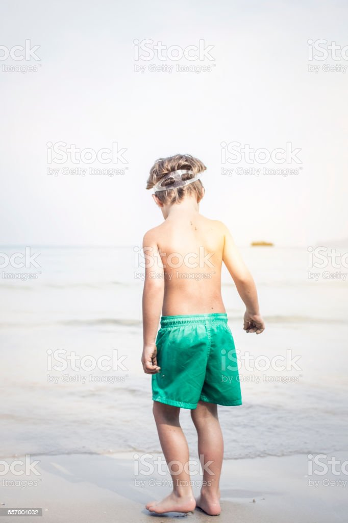 cute little boy with diving glasses at the beach, thailand stock photo
