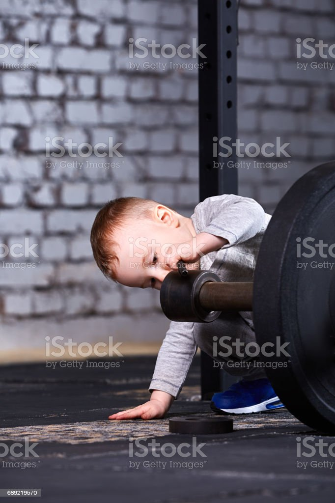 Cute little boy with dumbbells against brick wall in the    gym. stock photo