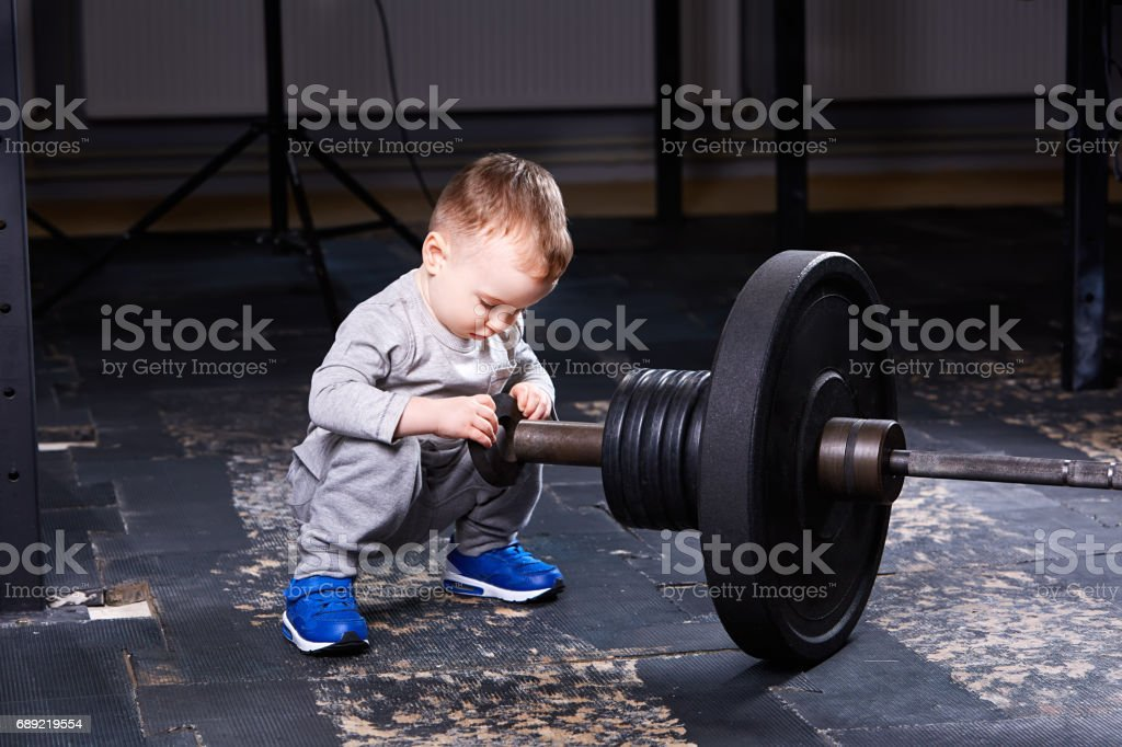 Cute little boy with dumbbells in the    gym. stock photo