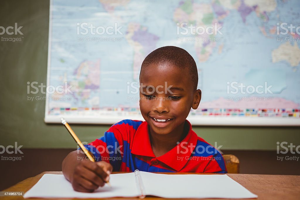 Cute little boy writing book in classroom stock photo