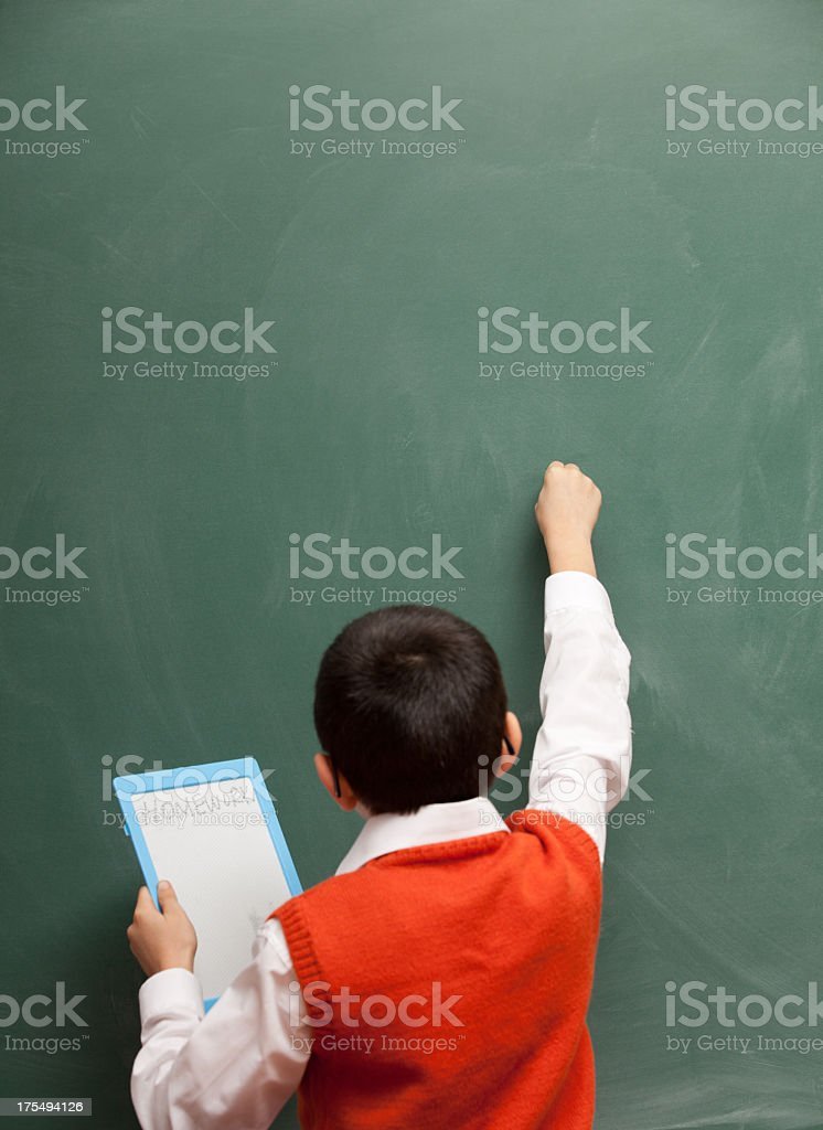 Cute Little Boy Writing On Blackboard While Holding Tablet Pc royalty-free stock photo