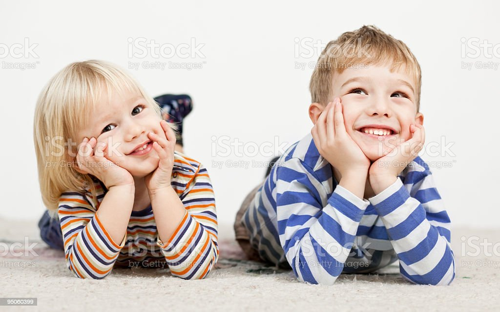 Cute little boys lying down on the floor and smiling royalty-free stock photo