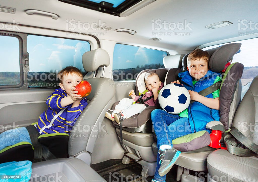 Cute little boys travelling by car in safety seats stock photo
