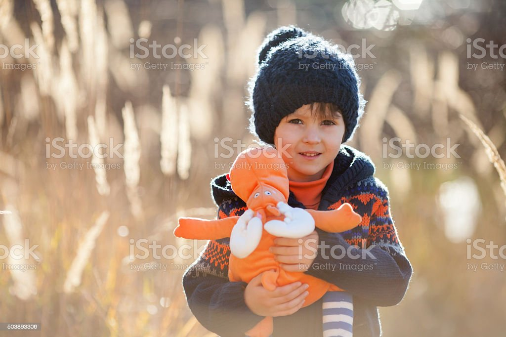 Cute little caucasian child, boy, holding fluffy toy, hugging it stock photo