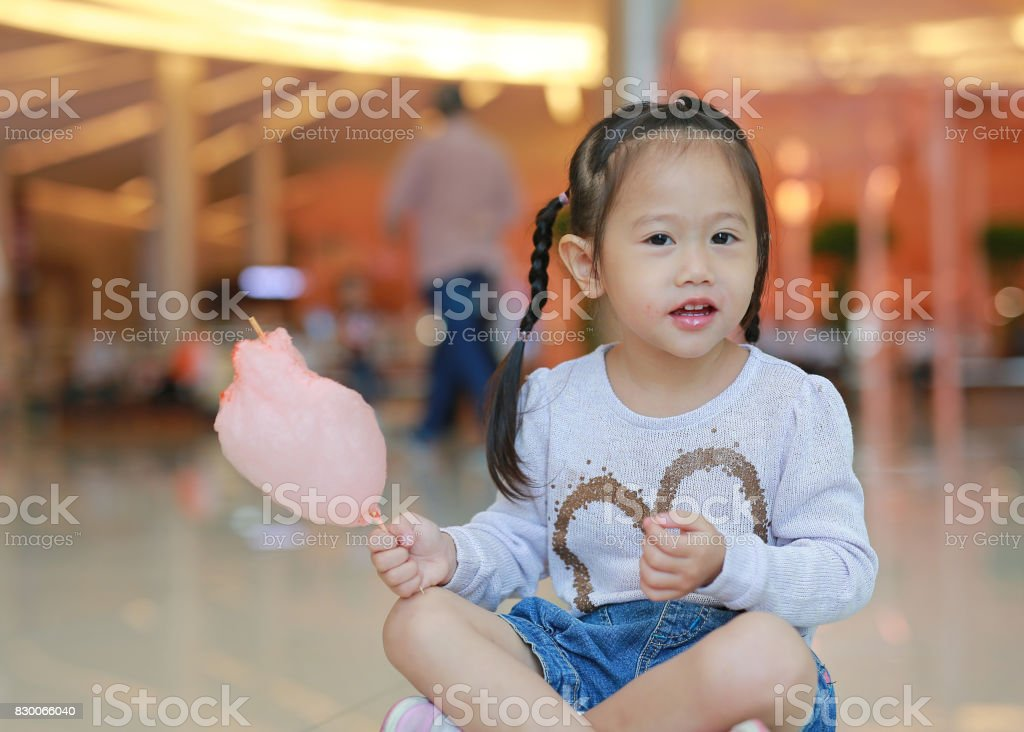 Cute Little child girl eating sweet spongy candy. stock photo