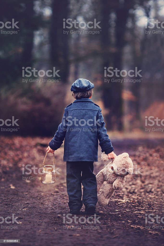 Cute little child, holding lantern and teddy bear in forest stock photo