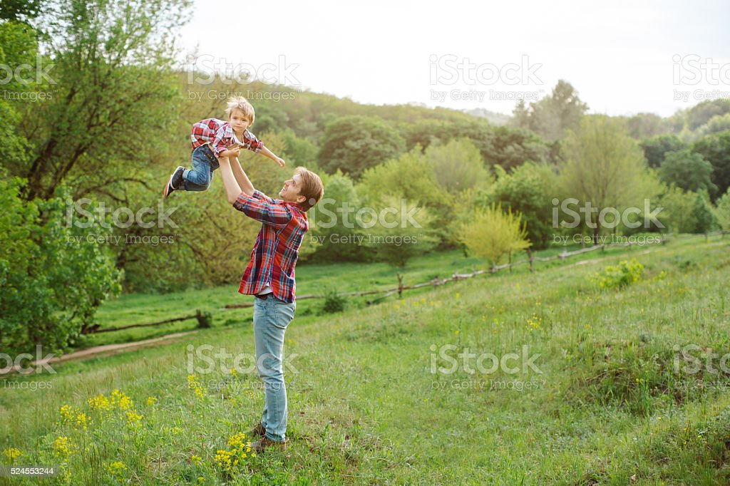 Cute little child playing outdoor with dad stock photo