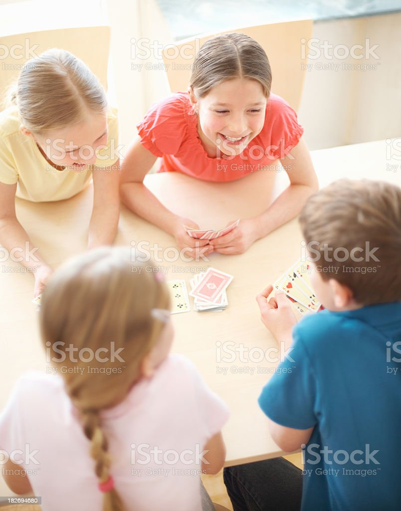 Cute little children playing a card game together royalty-free stock photo