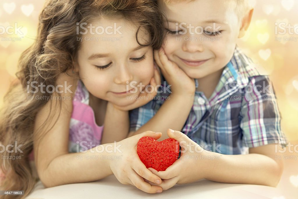 A cute little couple holding a red heart together  stock photo