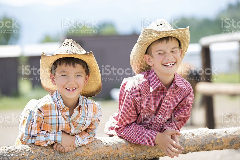 Cute little cowboys in hats leaning against fence post stock photo