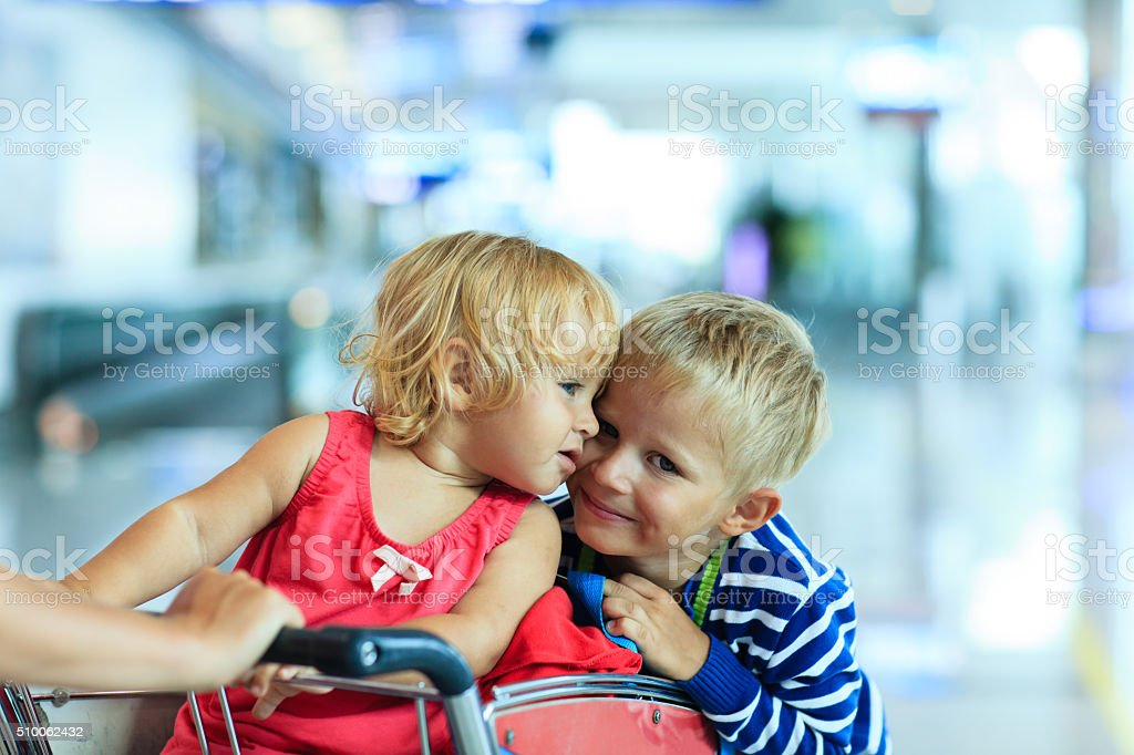 cute little girl and boy at airport on luggage cart stock photo