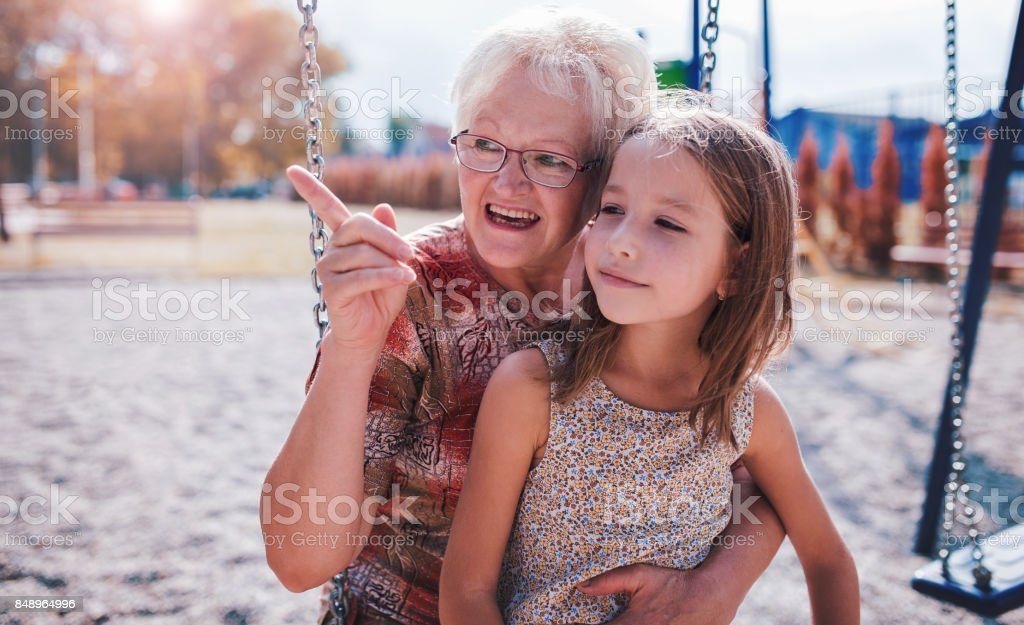 Cute little girl and her grandmother having fun on the playground in the park stock photo