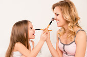 cute little girl and her mom doing each other maquillage