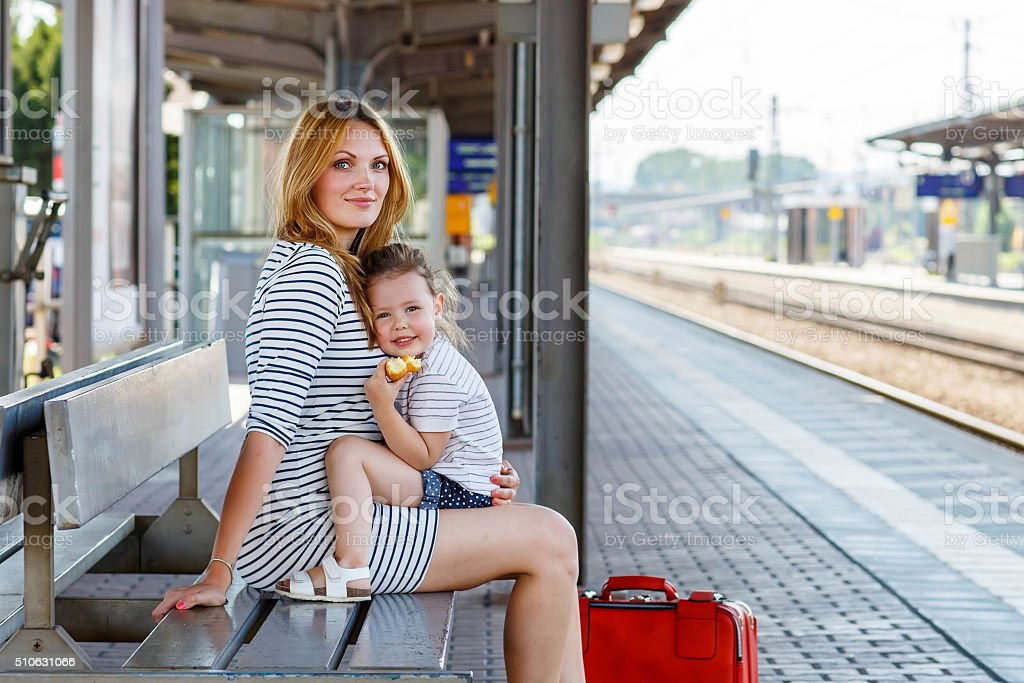 Cute little girl and mother on a railway station. stock photo