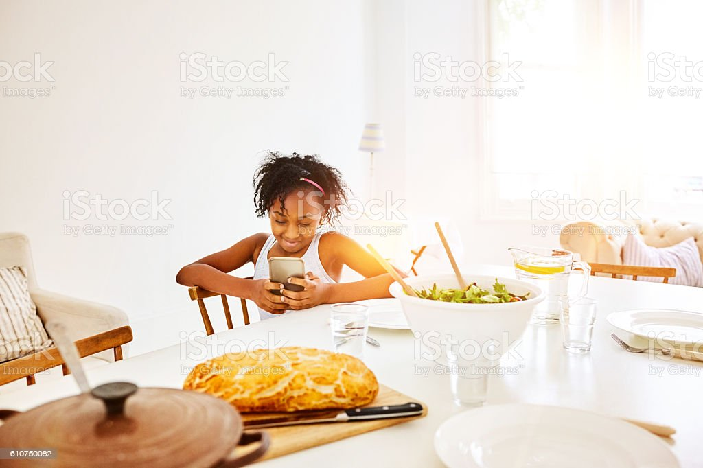 Cute little girl at dinner table using mobile phone stock photo
