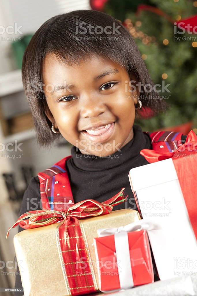 Cute Little Girl At Home Holding Christmas Presents royalty-free stock photo