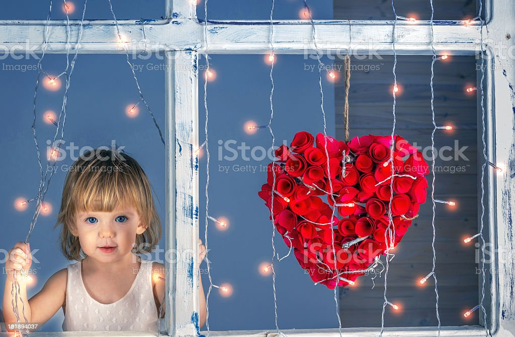 Cute little girl at the window with flower heart royalty-free stock photo