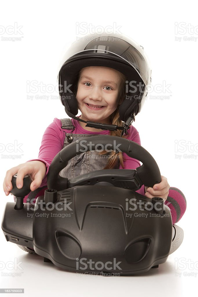 Cute little girl behind wheels of driving simulator royalty-free stock photo