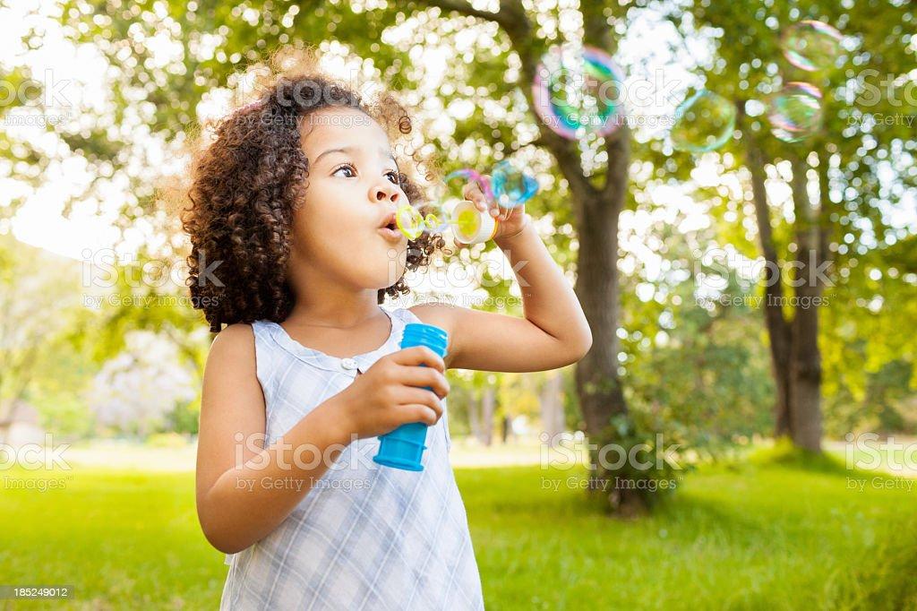 Cute Little Girl Blowing Bubbles stock photo