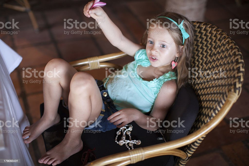 Cute little girl calling waiter in a restaurant royalty-free stock photo