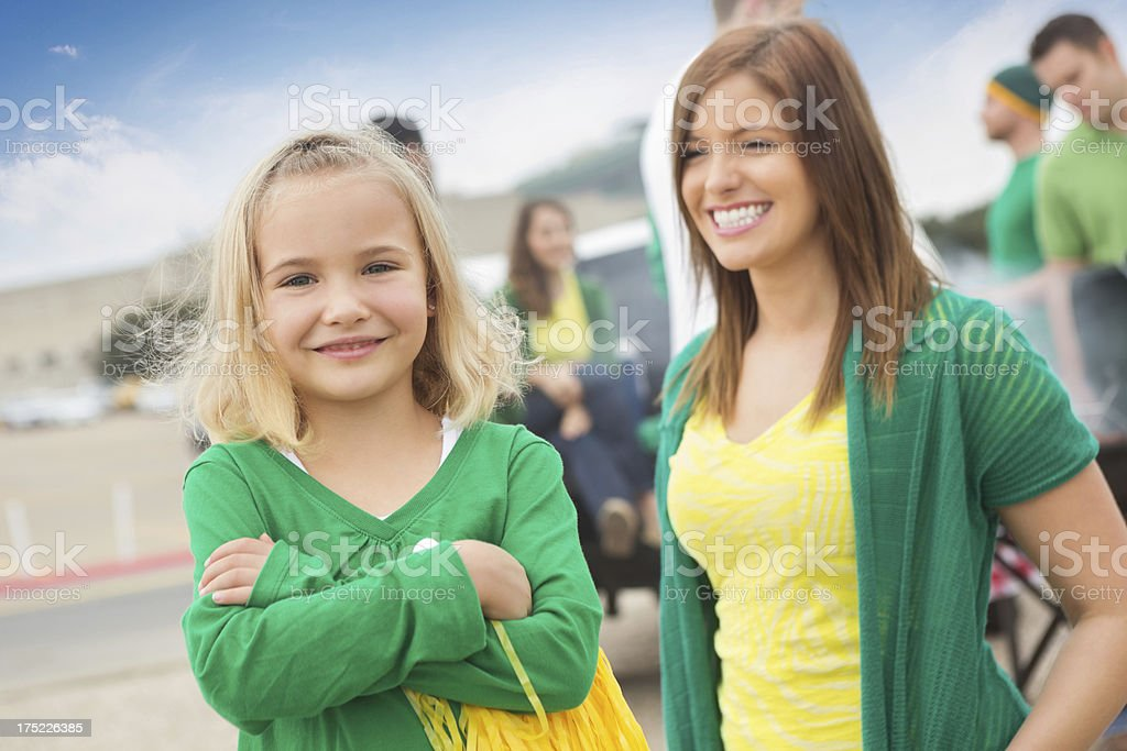 Cute little girl cheering for sports team, tailgating at stadium royalty-free stock photo
