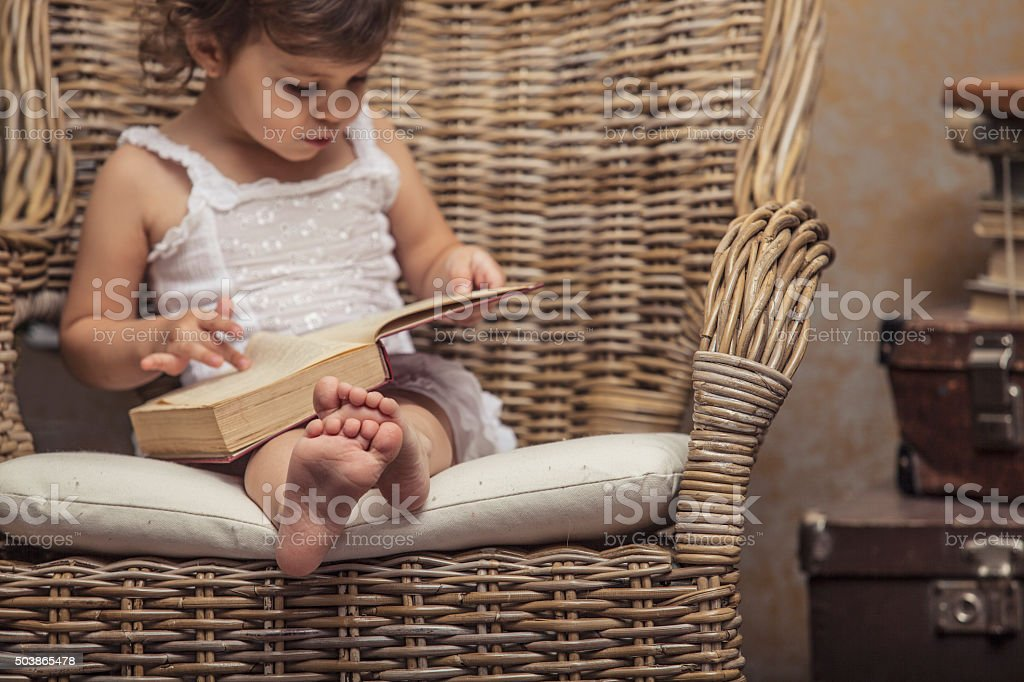 Cute little girl child in a chair, reading a book stock photo