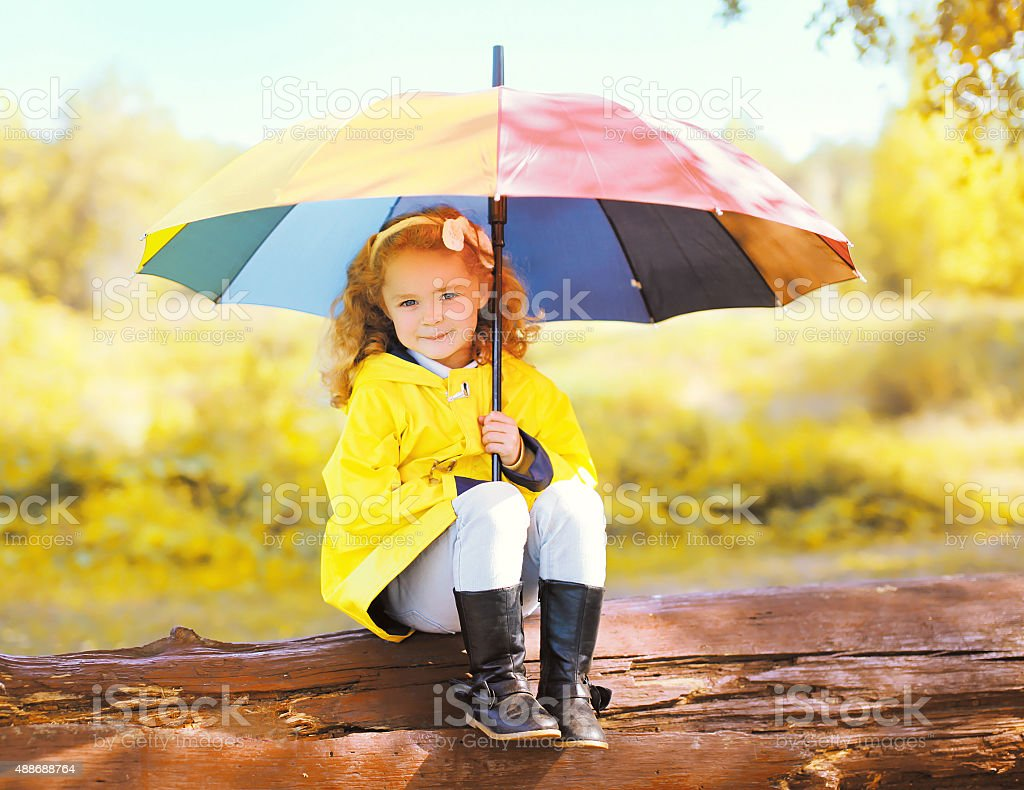 Cute little girl child with colorful umbrella in sunny autumn stock photo