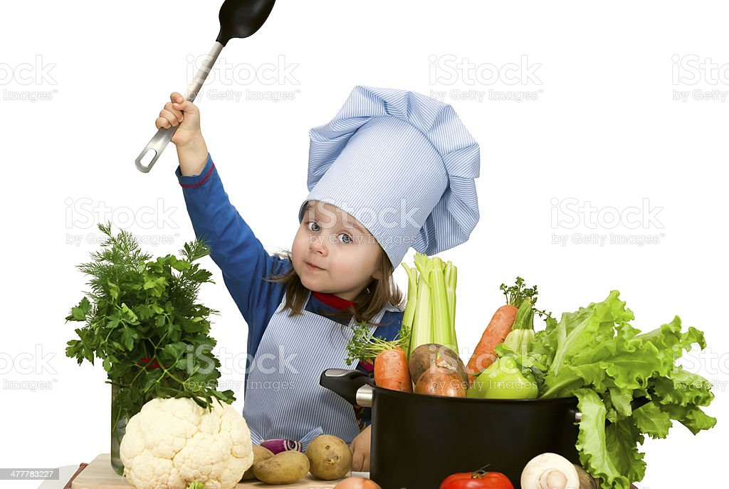 Cute little girl cooking soup with lots of different vegetables stock photo