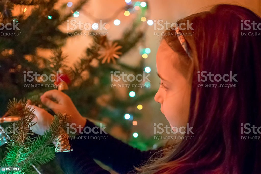 Cute little girl decorating Christmas tree at home stock photo