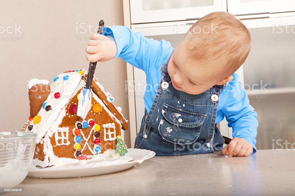 Cute Little Girl Decorating the Christmas Gingerbread House stock photo
