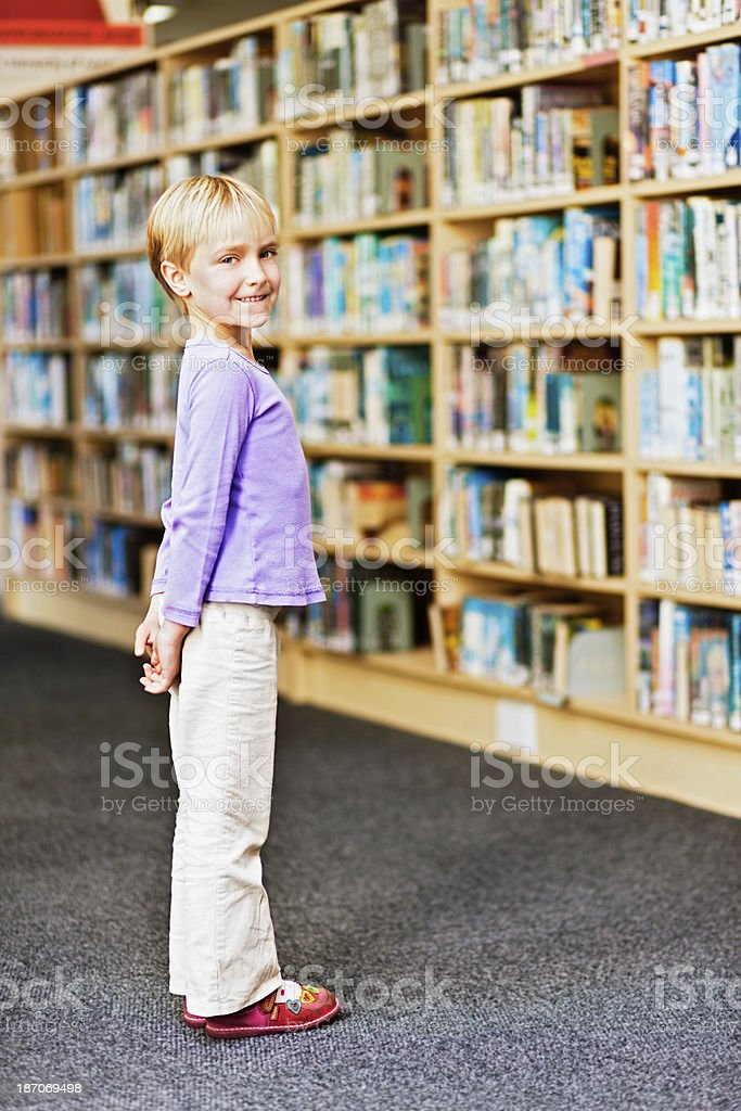 Cute little girl delighted by book choice in library royalty-free stock photo