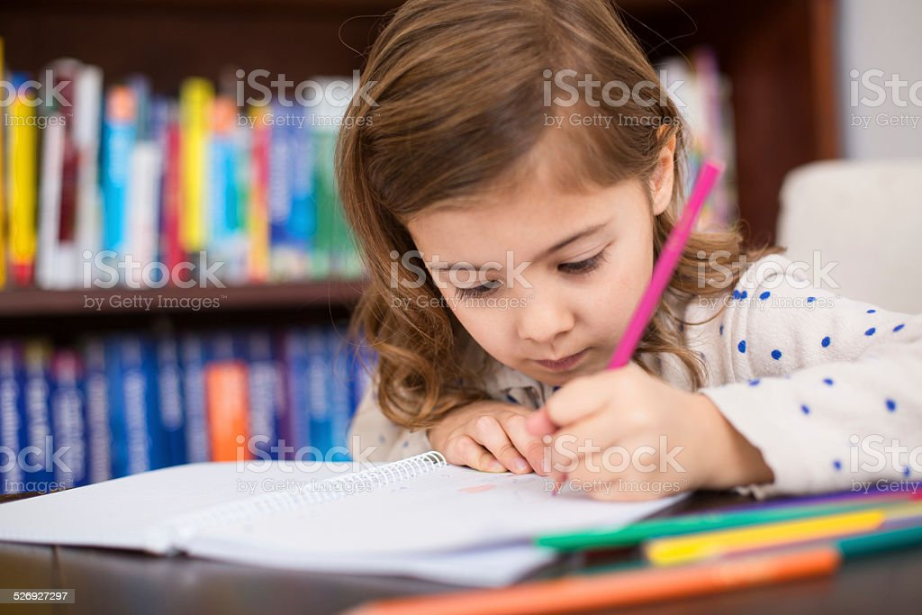 Cute little girl drawing with color pencils stock photo