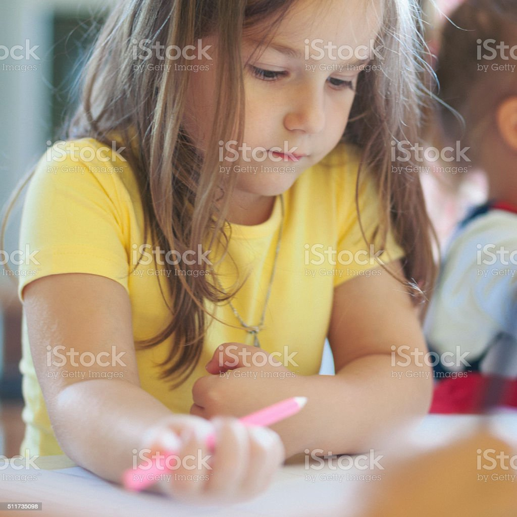 Cute little girl drawing with crayons stock photo