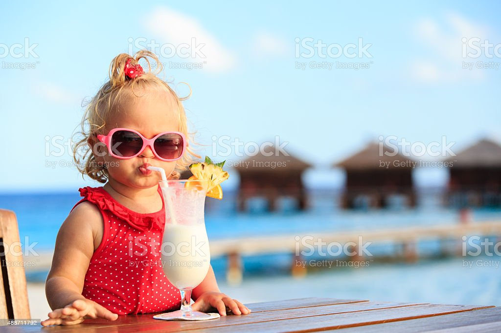 cute little girl drinking cocktail on tropical beach stock photo