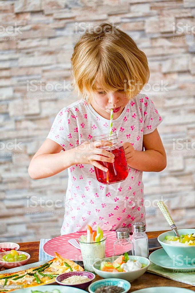 Cute Little Girl Drinking Fresh Grape Juice in a Jar stock photo