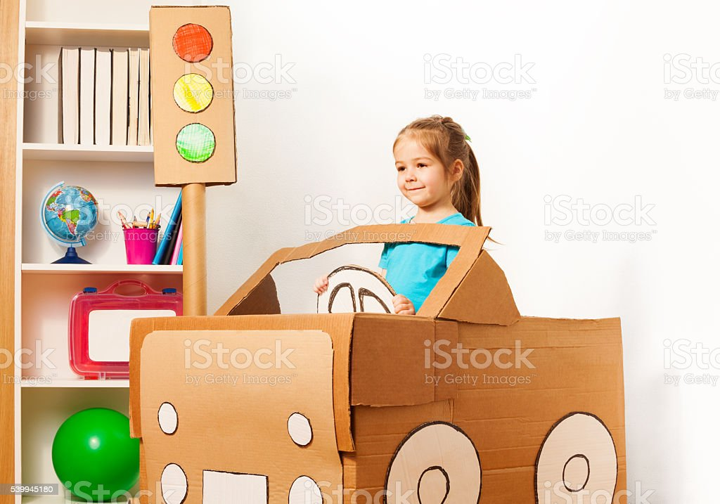 Cute little girl driving her toy cardboard car stock photo