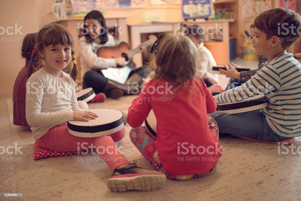 Cute little girl during a music class in a preschool. stock photo
