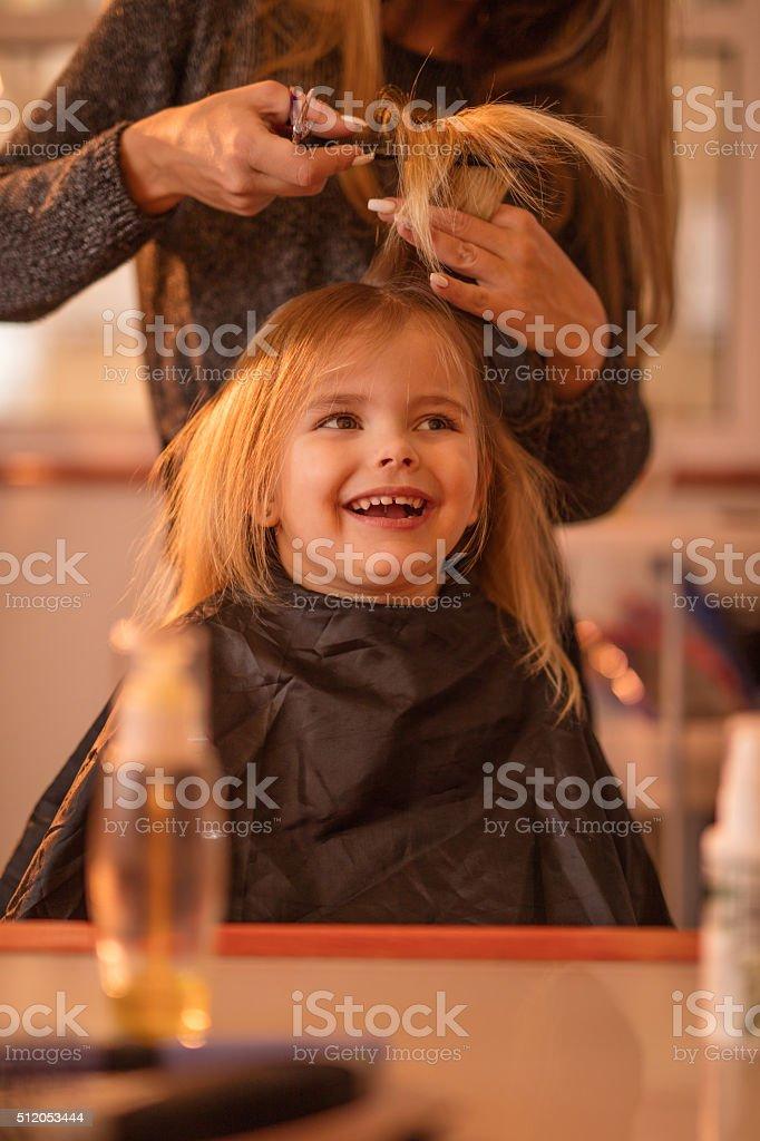 Cute little girl during hair cut at hair salon. stock photo