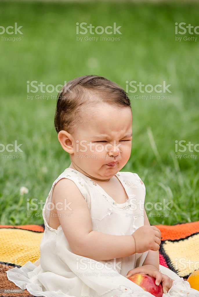 Cute little girl eating a sour apple stock photo