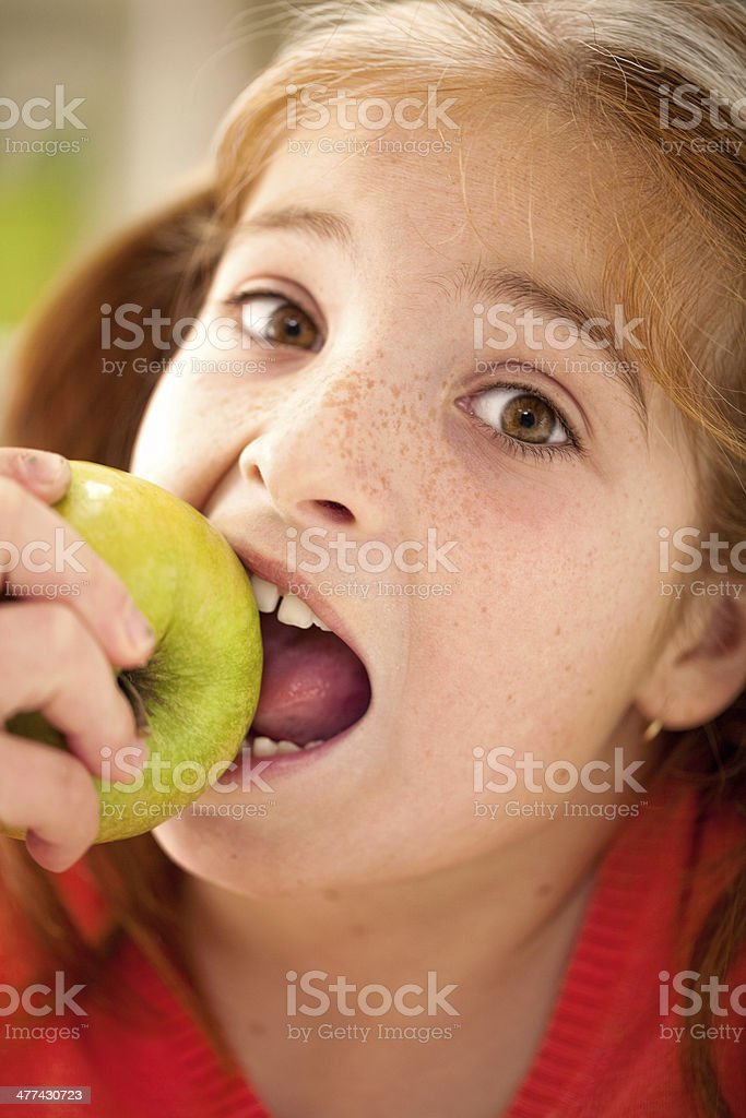 Cute little girl eating an apple royalty-free stock photo