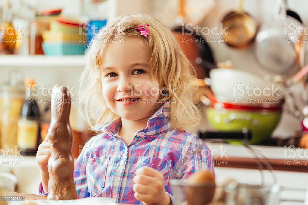Cute Little Girl Eating Chocolate Easter Bunny stock photo