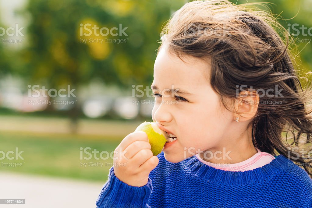 cute little girl eating fruit outdoors stock photo