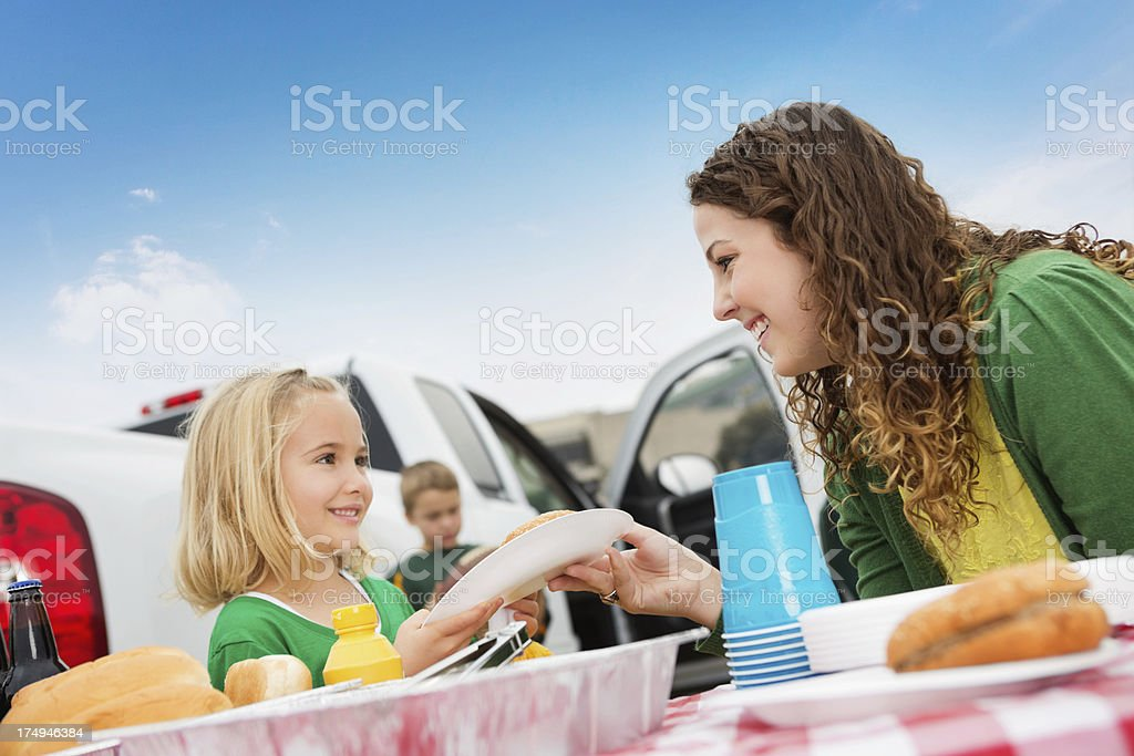 Cute little girl eating hamburger at football tailgate party royalty-free stock photo