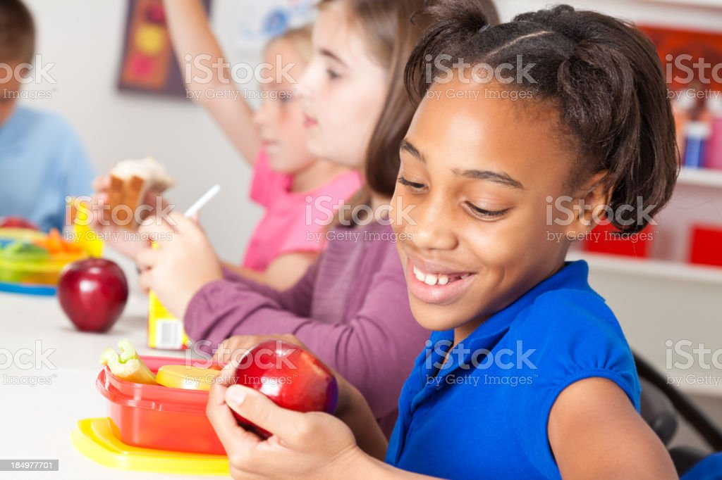 Cute little girl eating lunch at school royalty-free stock photo