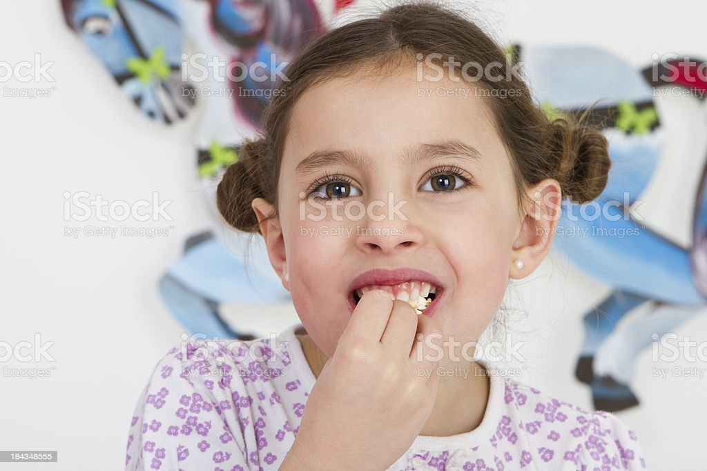 Cute little girl eating pop-corn - studio shot royalty-free stock photo