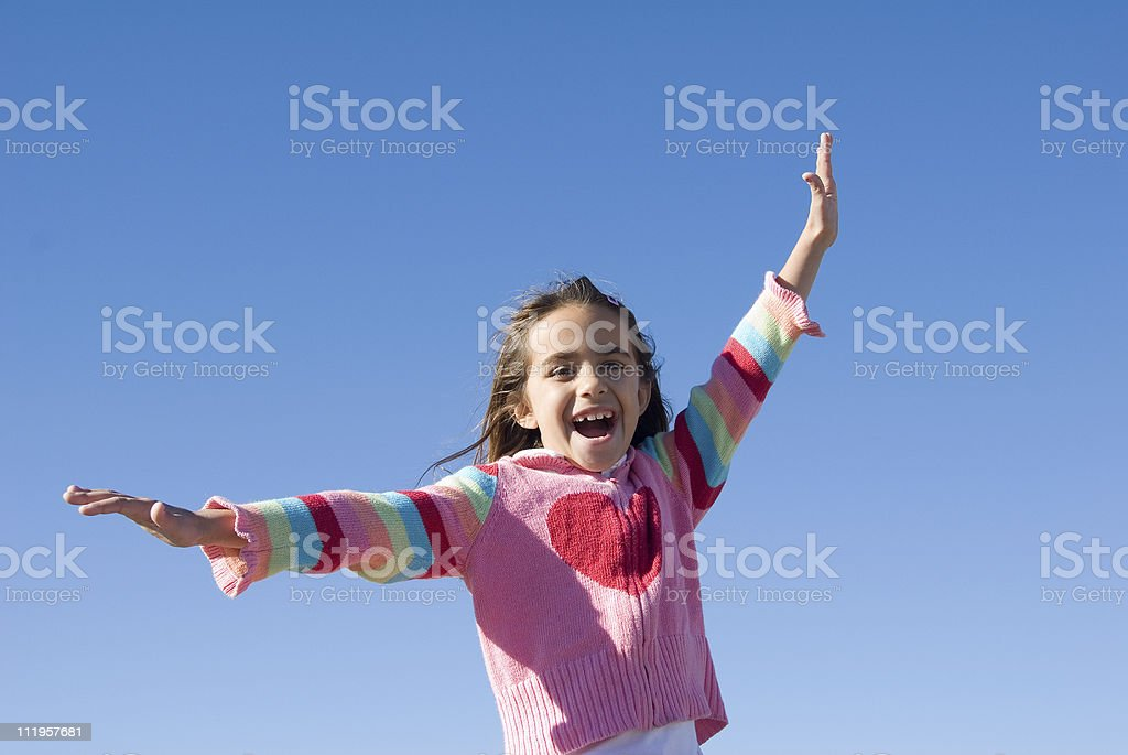 Cute little girl flying in the blue sky royalty-free stock photo