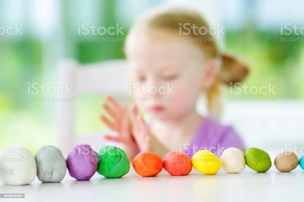Cute little girl having fun with modeling clay at a daycare. Creative kid molding at home. stock photo