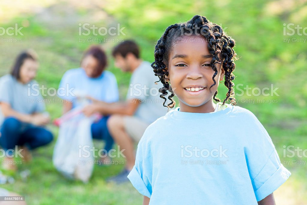 Cute little girl helping family clean up park stock photo