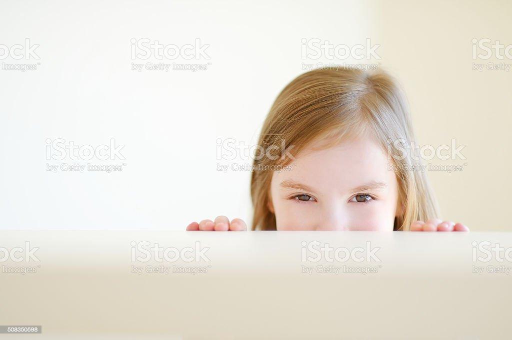 Cute little girl hiding under a table stock photo